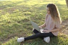 十几岁的女孩坐有膝上型计算机的草坪 库存照片