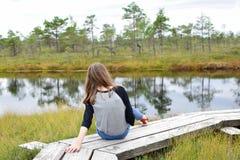 十几岁的女孩坐木路 库存图片