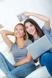 十几岁的女孩坐看膝上型计算机的长沙发 免版税库存图片