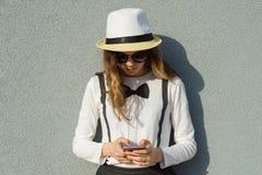 十几岁的女孩室外画象帽子的,女孩使用智能手机,读,写消息,灰色织地不很细墙壁背景 库存照片