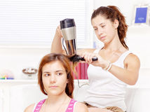十几岁的女孩干毛发给她的朋友 免版税图库摄影