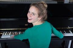 十几岁的女孩弹在绿色衬衣的钢琴 库存照片