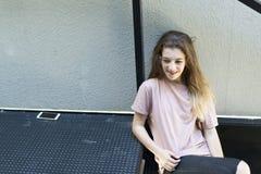 十几岁的女孩微笑的坐金属楼梯 库存照片