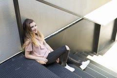 十几岁的女孩微笑的坐金属楼梯 免版税图库摄影