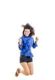 十几岁的女孩或妇女愉快为她的在蓝色空白的衬衣的成功 免版税库存图片