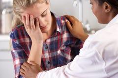 十几岁的女孩拜访Office Suffering With Depression医生的 库存照片