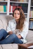 十几岁的女孩是哭泣的坐长沙发 免版税库存照片