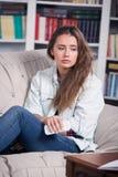 十几岁的女孩是哭泣的坐长沙发 免版税库存图片