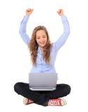十几岁的女孩欢呼,当使用膝上型计算机时 库存图片