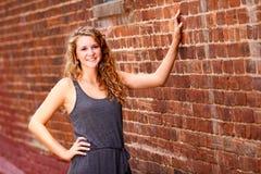 十几岁的女孩灰色礼服砖墙 图库摄影