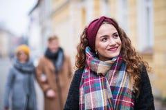 十几岁的女孩画象有头饰带和围巾的在街道上在冬天 免版税库存图片