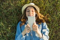 十几岁的女孩画象说谎在草的14岁 礼服帽子的女孩,在她的耳机拿着一个智能手机,听musi 库存照片