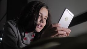 十几岁的女孩网络购物在她的智能手机在床上夜间看 小青少年的敞篷女孩写一则消息 影视素材