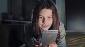 十几岁的女孩网络购物在她的智能手机在床上夜间看 小青少年的敞篷女孩写一则消息 股票录像