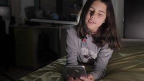 十几岁的女孩网络购物在她的智能手机在床上夜间看 小青少年的敞篷女孩写一则消息 股票视频