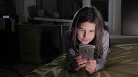 十几岁的女孩网络购物在她的智能手机在床上夜间看 小青少年的生活方式敞篷女孩写a 股票视频