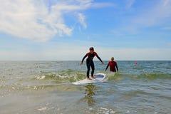 年轻十几岁的女孩获得与冲浪的教训的乐趣 免版税库存照片