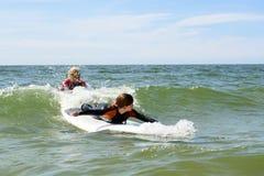 年轻十几岁的女孩获得乐趣在度假与冲浪的教训的 免版税库存图片