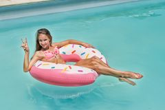 十几岁的女孩获得在可膨胀的多福饼的乐趣在蓝色游泳池 库存照片