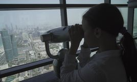 十几岁的女孩通过从观察台的阿布扎比望远镜看 免版税图库摄影
