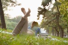 十几岁的女孩阅读书在公园 免版税库存照片