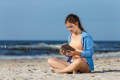 十几岁的女孩阅读书坐海滩 免版税库存图片