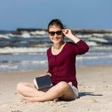 十几岁的女孩阅读书坐海滩 库存照片
