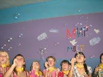 十几岁的女孩队节日吹的泡影的 库存照片