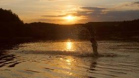 十几岁的女孩飞溅水在日落 免版税库存图片