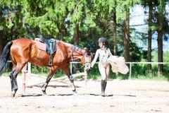 十几岁的女孩骑马者在骑马术学校地方 库存图片