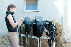 十几岁的女孩骑马者清洗黑皮革马马鞍 免版税库存图片