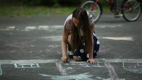 十几岁的女孩画与在路面的白垩在街道 股票视频