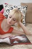 十几岁的女孩读书杂志在床上 免版税库存图片