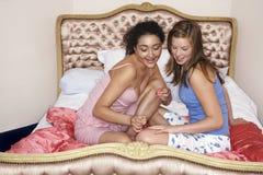 十几岁的女孩绘画在床上的朋友的指甲盖 免版税库存图片