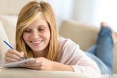 年轻十几岁的女孩说谎的沙发文字笔记 库存图片