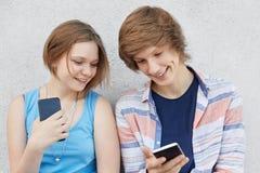 十几岁的女孩画象有浮动的头发的在蓝色礼服和他的男性朋友显示她某事在聪明电话微笑的衬衣的 免版税库存照片