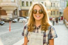 十几岁的女孩13, 14岁,城市街道背景室外画象  免版税库存图片