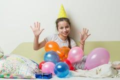 十几岁的女孩` s生日是10岁 一个欢乐帽子的一个女孩说谎与在床上的一件礼物在儿童` s屋子,女孩展示 库存照片