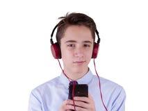 十几岁的男孩佩带的耳机和听到音乐,沟通由电话 背景查出的白色 免版税图库摄影
