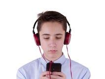 十几岁的男孩佩带的耳机和听到音乐,沟通由电话 背景查出的白色 免版税库存图片