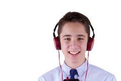 十几岁的男孩佩带的耳机和听到音乐,沟通由电话 背景查出的白色 库存图片