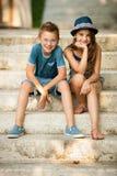 十几岁的男孩和女孩坐台阶在公园 免版税库存图片