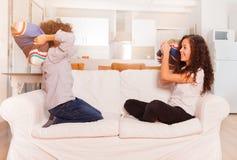 十几岁的男孩和女孩把战斗在长沙发枕在 免版税库存照片