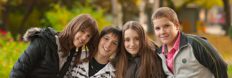 十几岁的男孩和女孩获得乐趣在公园在美好的秋天天 免版税库存图片