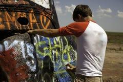 十几岁的男孩喷漆汽车 库存照片