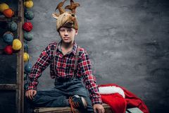 十几岁的男孩在一件格子花呢上衣和一个帽子穿戴了有圣诞节鹿` s垫铁的 免版税库存照片