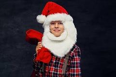 十几岁的男孩在圣诞老人` s假日服装穿戴了 库存照片