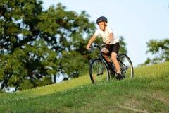 十几岁的男孩在城市公园骑从小山的一辆自行车 库存照片