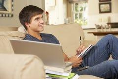 十几岁的男孩在家坐做家庭作业的沙发使用便携式计算机,看电视 库存照片