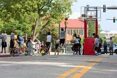 十几岁的男孩在沥青在城市街道上的篮球比赛竞争 免版税库存图片